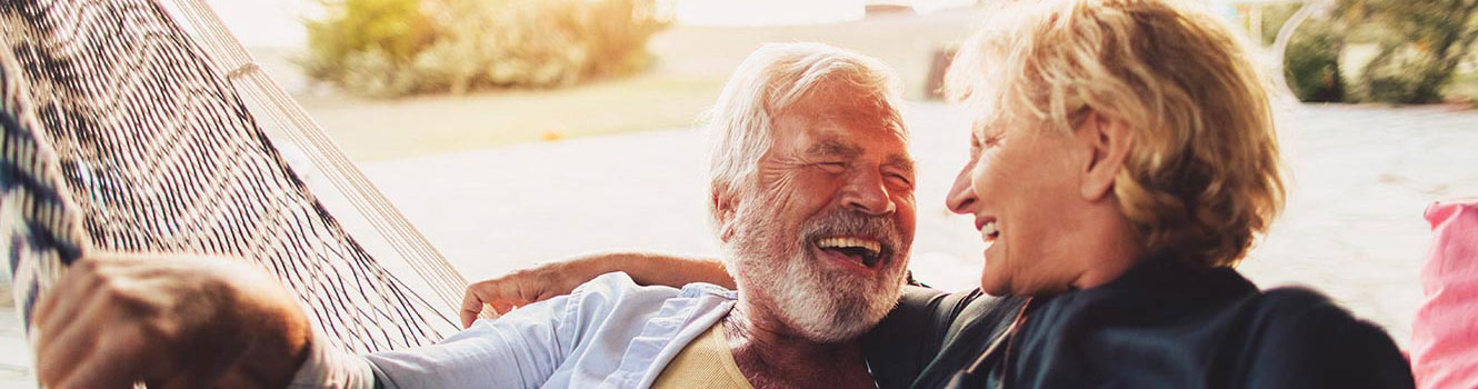An elderly man and woman relaxing on a hammock and laughing at a joke.