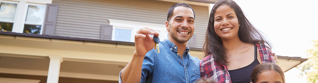 A man and a woman holding keys in front of their new house.