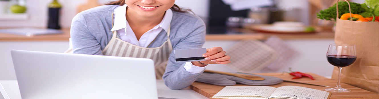 Stock photo of woman on laptop in kitchen doing her banking.