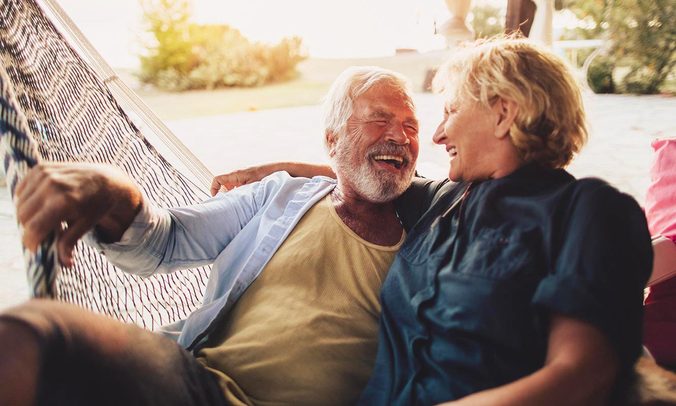 A elderly adult couple relaxing and laughing on a hammock.
